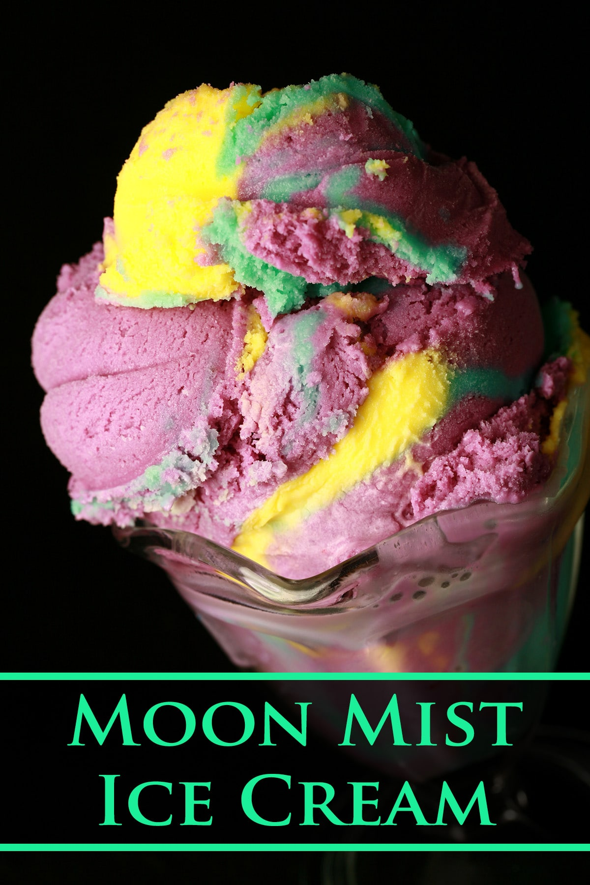 A fluted glass dessert bowl is stacked high with scoops of homemade moon mist ice cream - purple, blue, and yellow marbled ice cream.