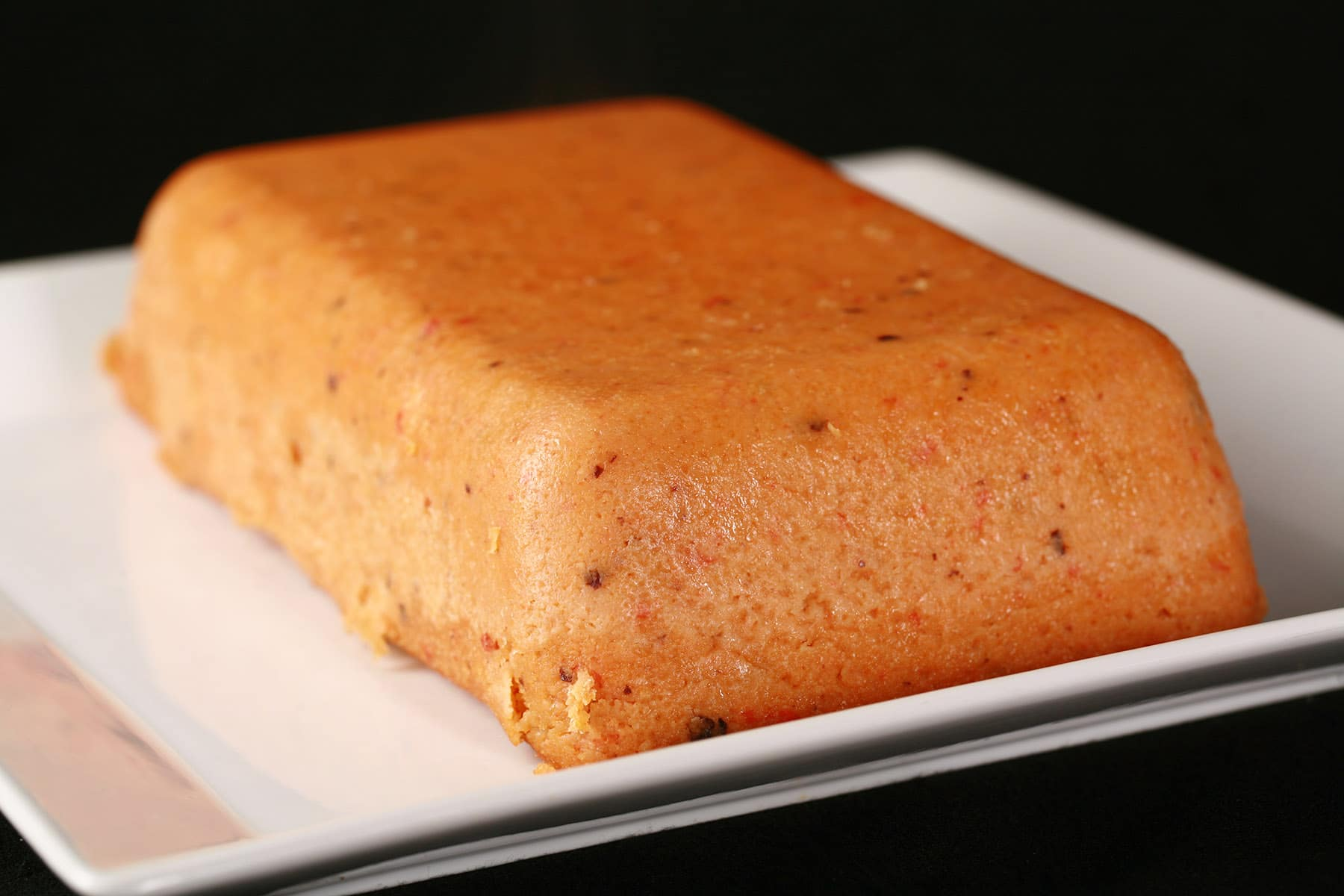A loaf of pink moin-moin, on a white plate.