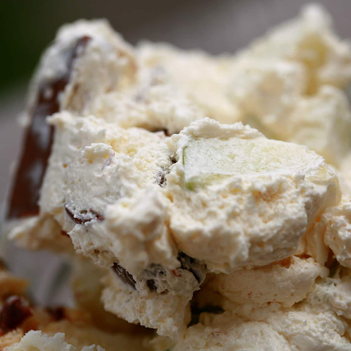 A fluted dessert bowl with Canadian Candy Bar Salad - an off-white, fluffy whipped cream based dessert with chunks of apple and candy bar visible throughout.
