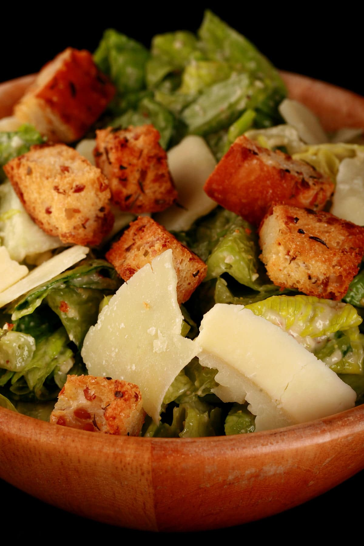 "A bowl of ""extreme"" caesar salad, with big flakes of Parmesan cheese, and croutons."