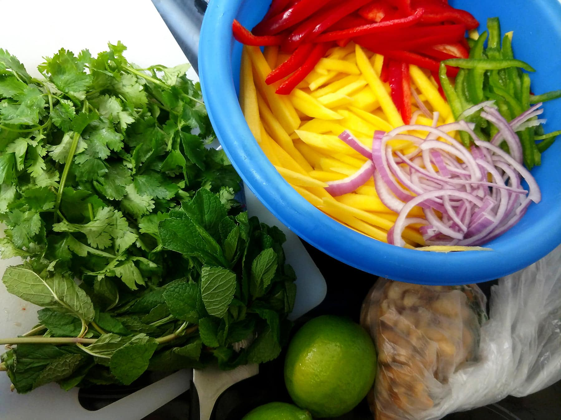 A blue mixing bowl holds slices of mango, red and green peppers, and red onions. Cilantro and mint is shown on a cutting board beside it.