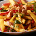 A close up view of Mango Salad - thin sticks of mango, red pepper, green pepper, red onions, and cashews. It's dressed with lime juice and pieces of cilatro and mint.