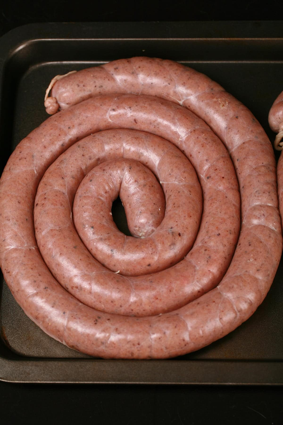 A large coil of raw sausage, on a cookie sheet.