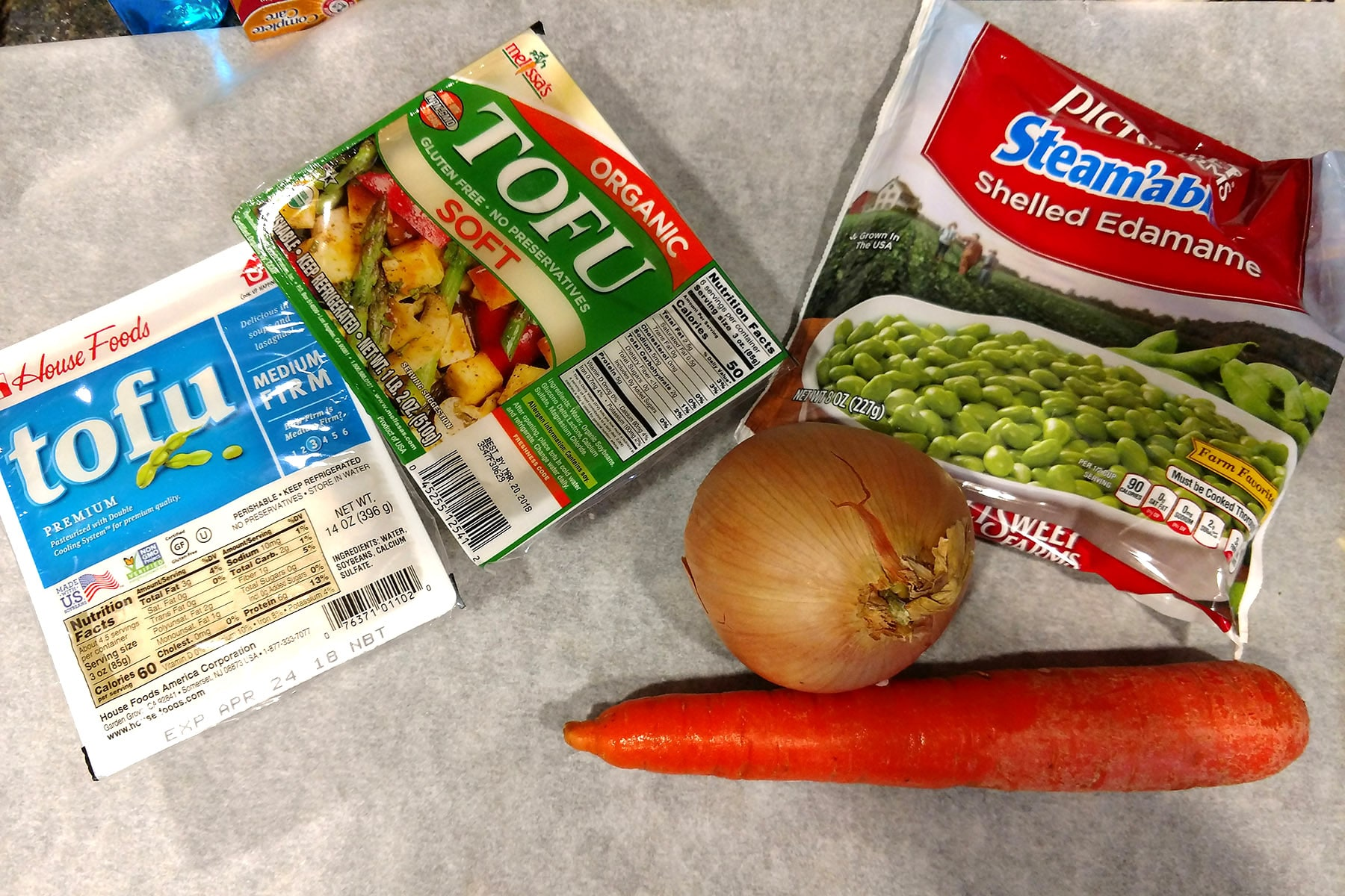 A carrot, an onion, a bag of frozen edamame, and 2 packs of tofu on a countertop.