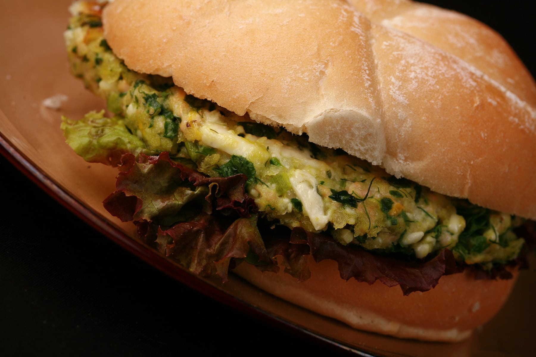 A salmon burger with spinach and feta visible in the patty. It's on a kaiser bun, with red lettuce under the patty.