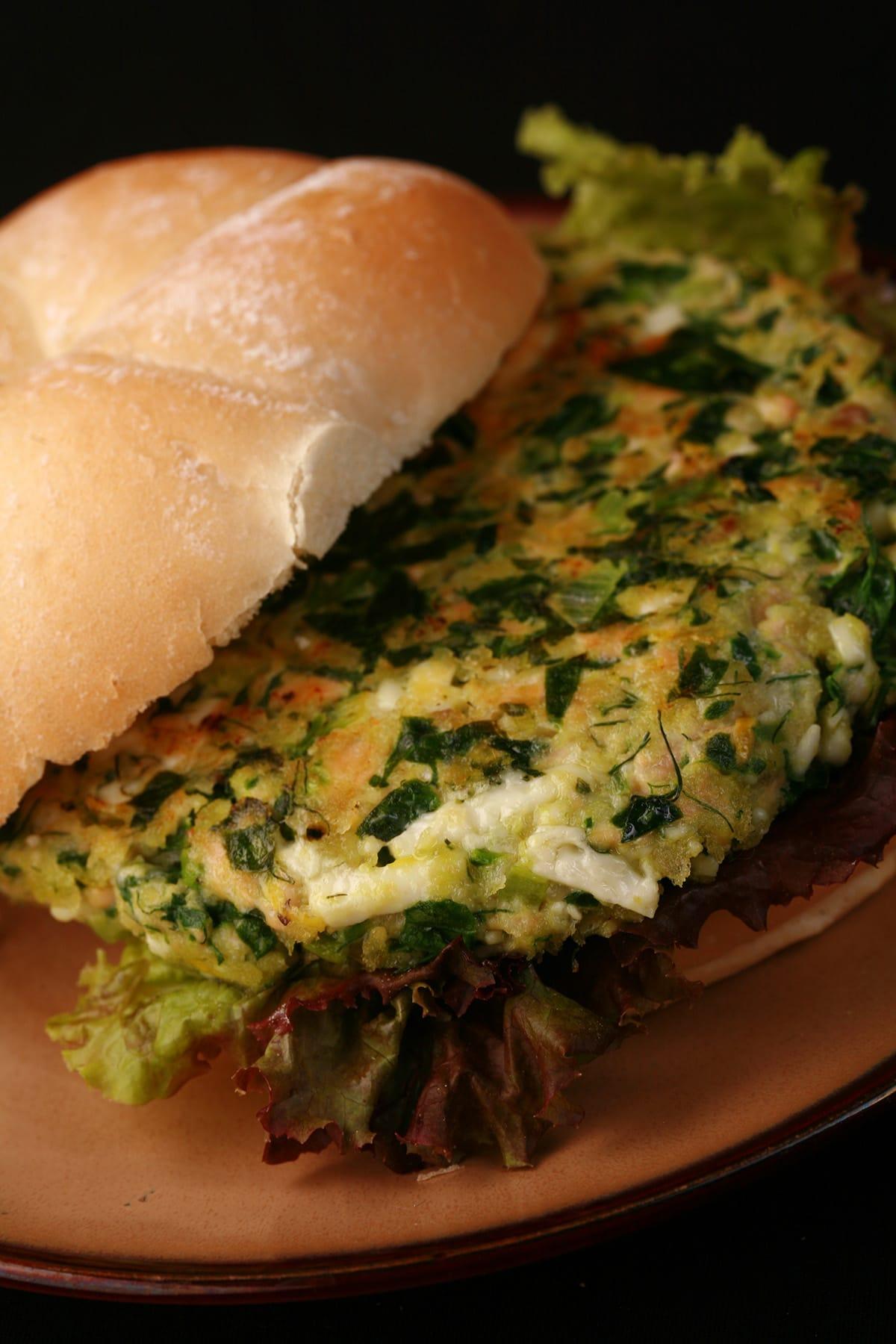 A salmon feta salmon burger, on a kaiser bun, with red lettuce under the patty.