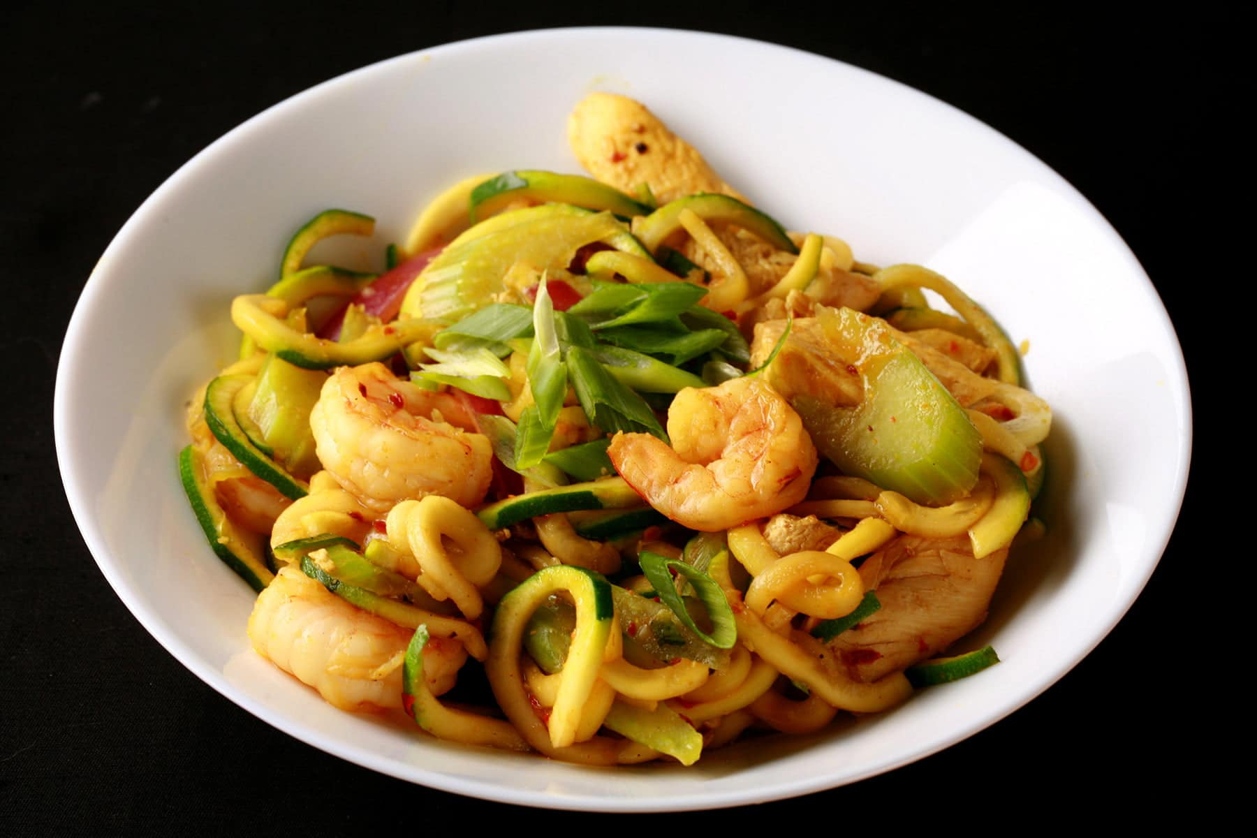 A white bowl with singapore mai fan style zoodles.