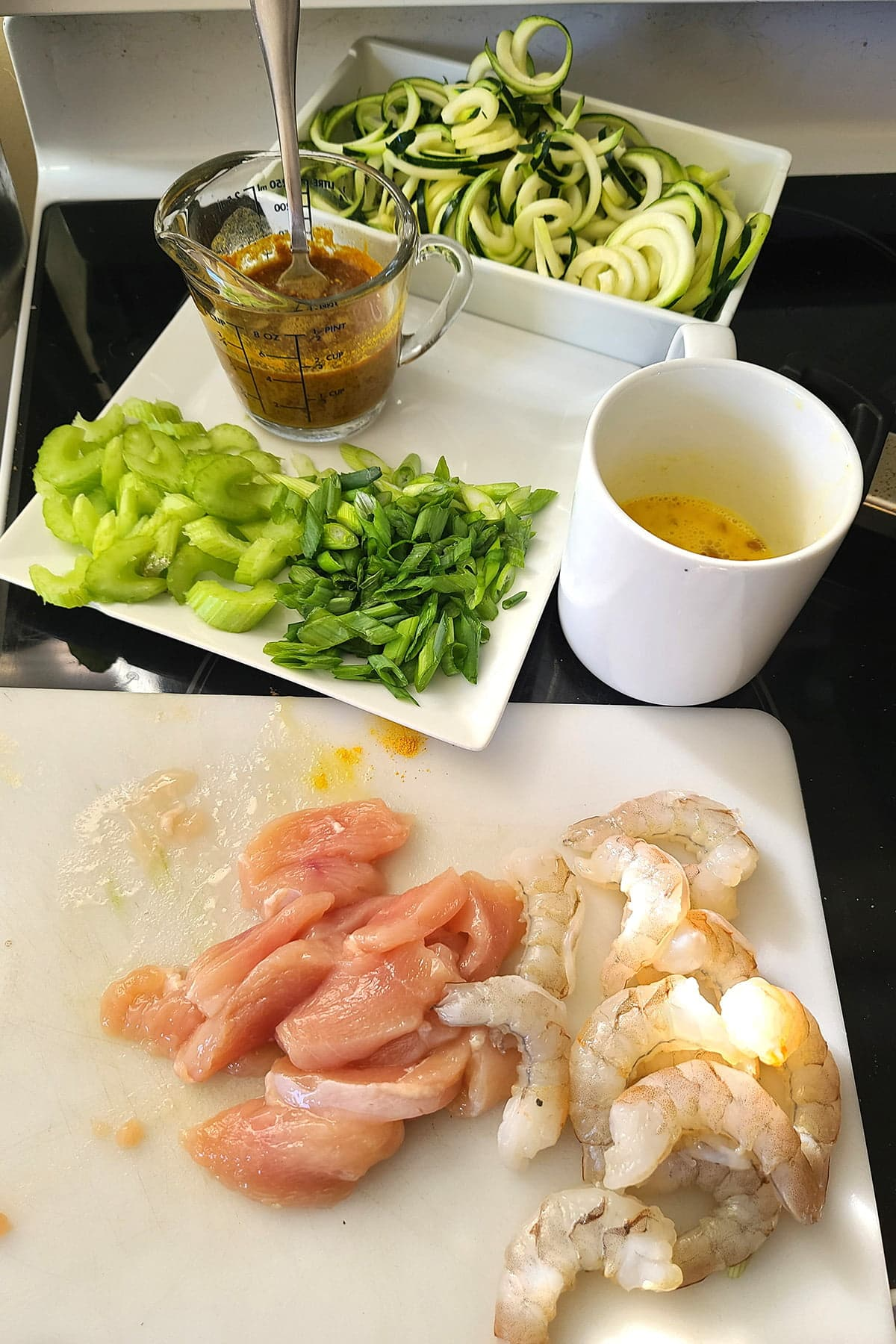 Prepped items: chicken and shrimp on a cutting board, celery and green onions on a plate, sauce in a measuring cup, egg mixture in a mug, and zoodles in a plastic container.