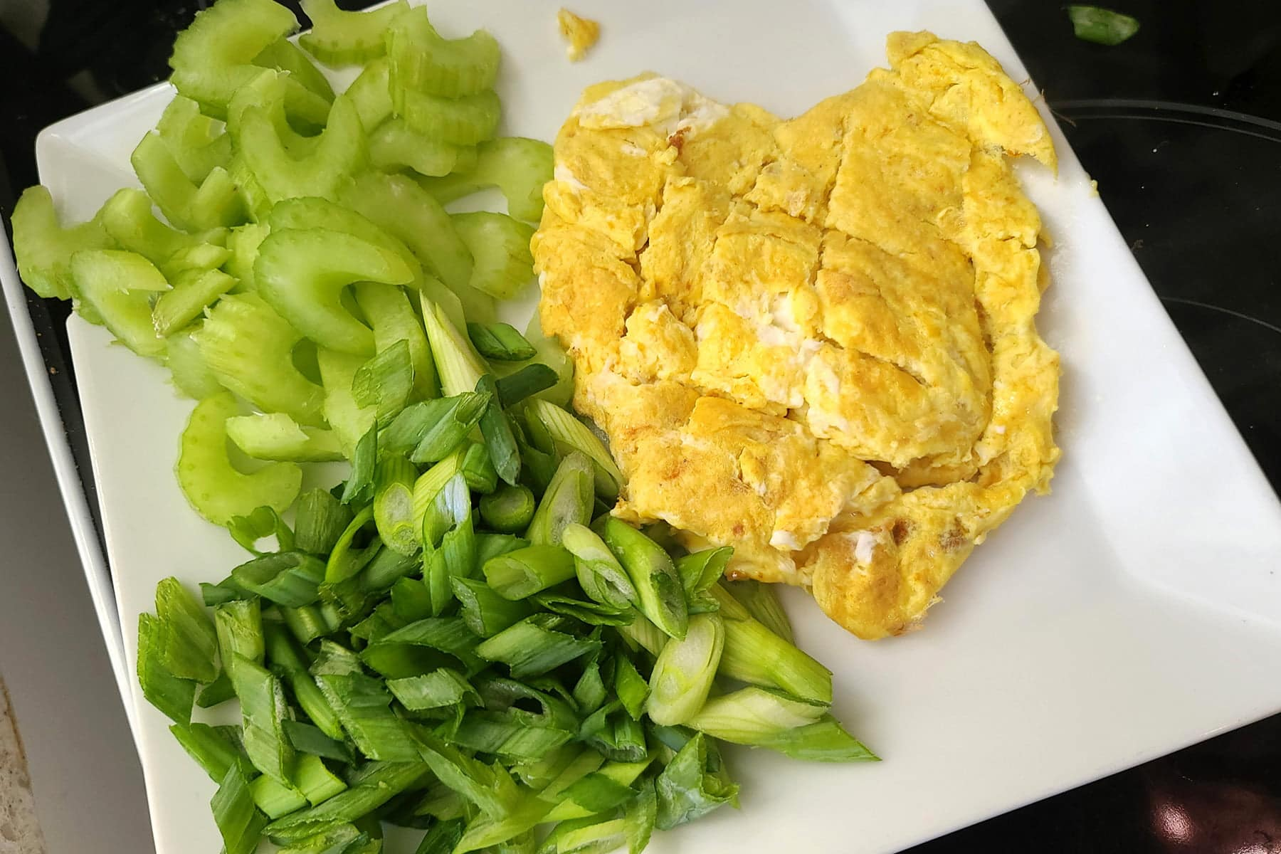A white plate with scrambled eggs, celery, and green onions on it.