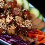 Cubes of sesame crusted smoked tofu on top of a colourful salad. Cucumbers, beets, carrots, and purple cabbage are visible.