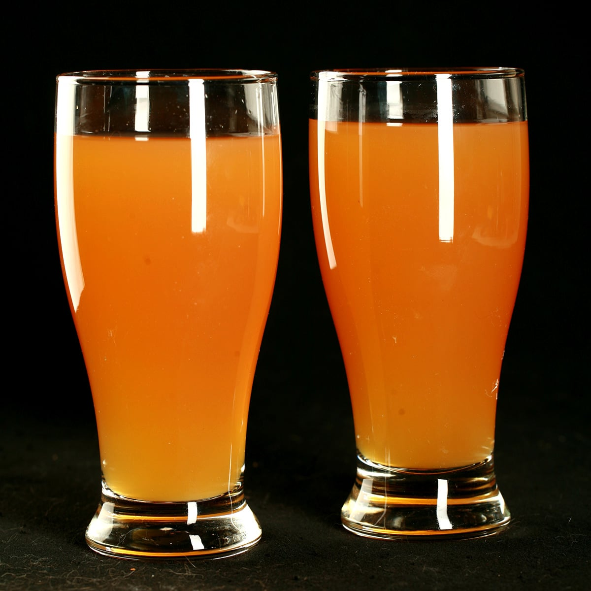 Two glasses of homemade Beep Drink - a orange coloured juice drink - against a black background.