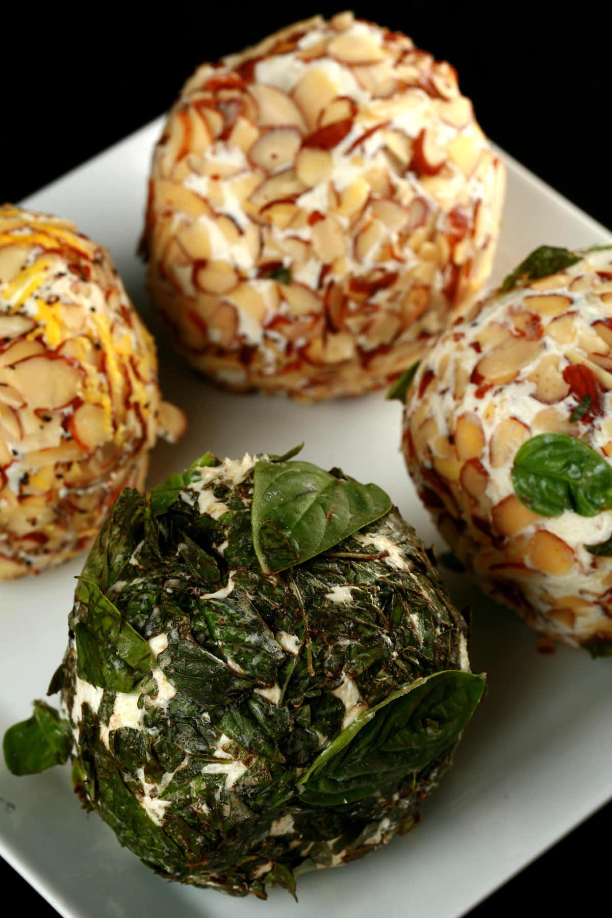 4 cheese balls with a variety of coatings - nuts, seeds, and basil - are arranged on a plate.