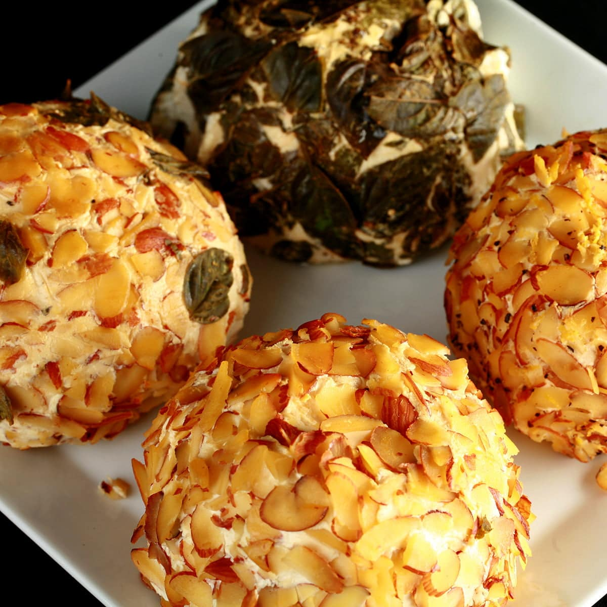 4 smoked cheese balls - with various coatings - are arranged on a plate.