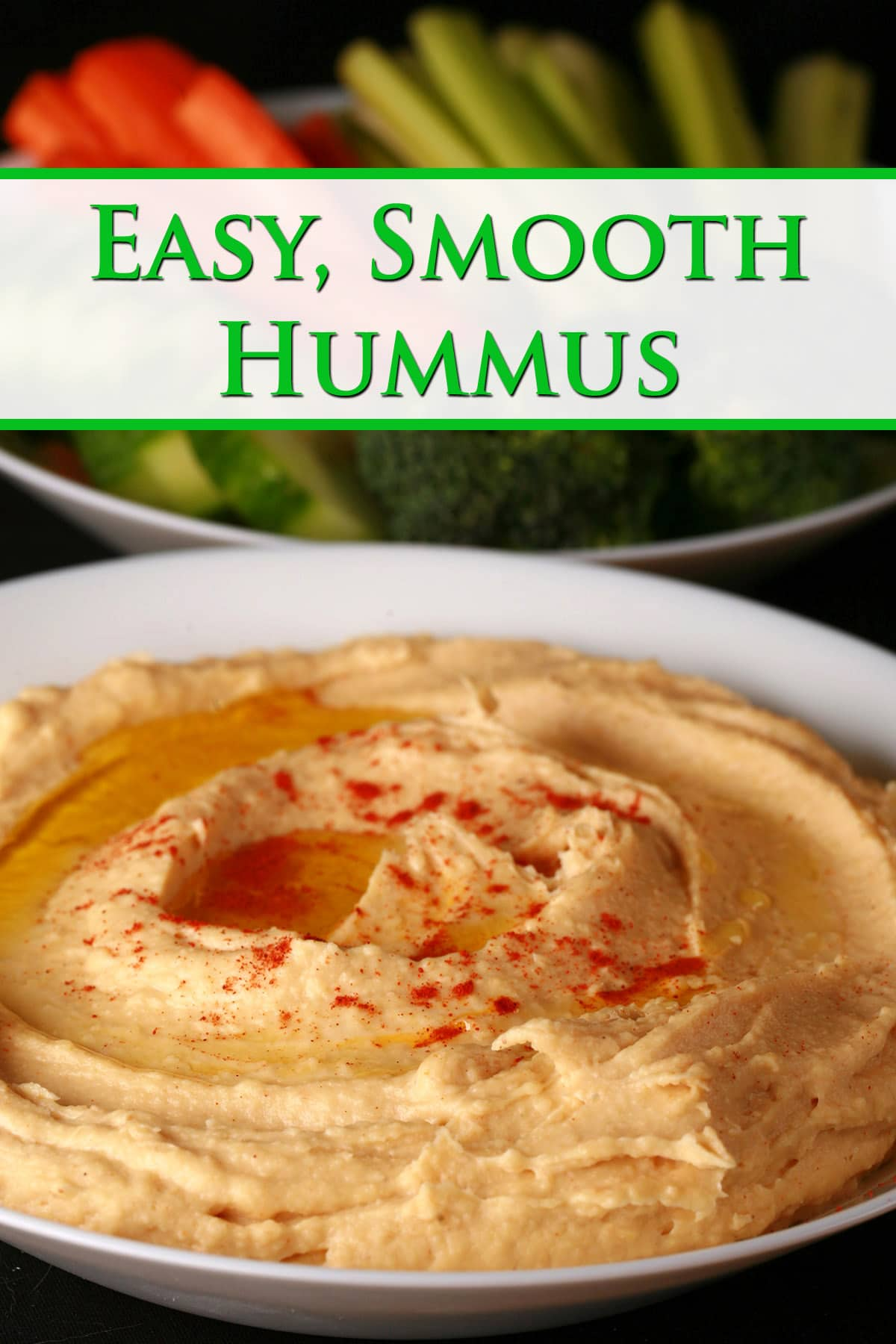 A white bowl of smooth hummus.  There is olive oil and a sprinkling of paprika on top, and a bowl of vegetable dippers next to it.  Green text overlay says Easy smooth hummus.