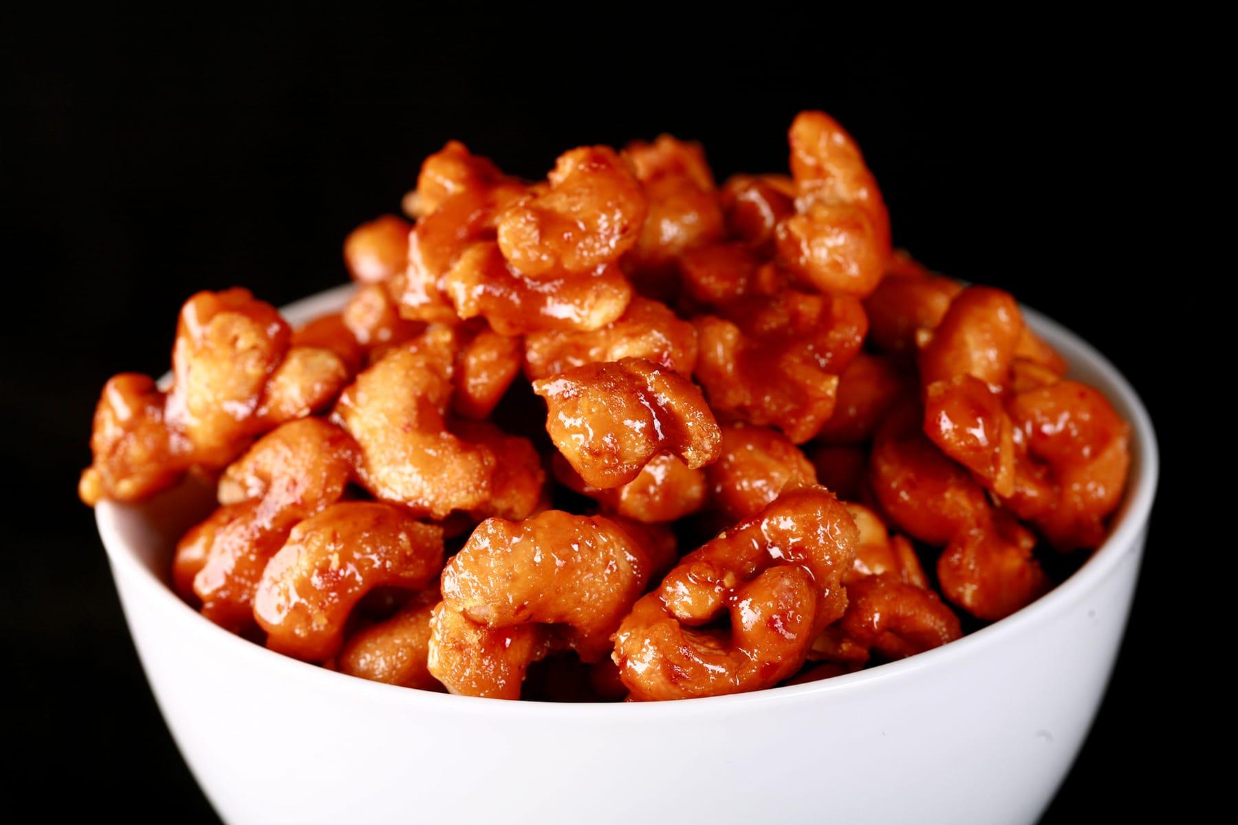 A round white bowl full of honey sriracha glazed cashews.