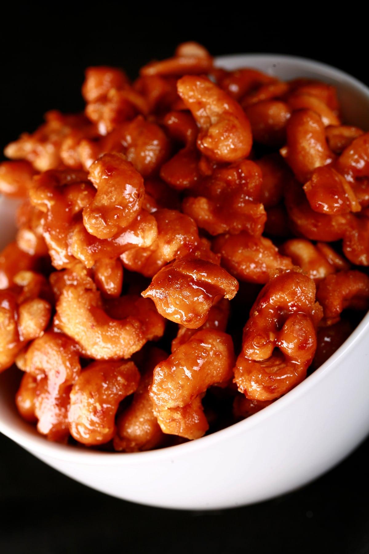 A round white bowl full of honey jeow glazed cashews.