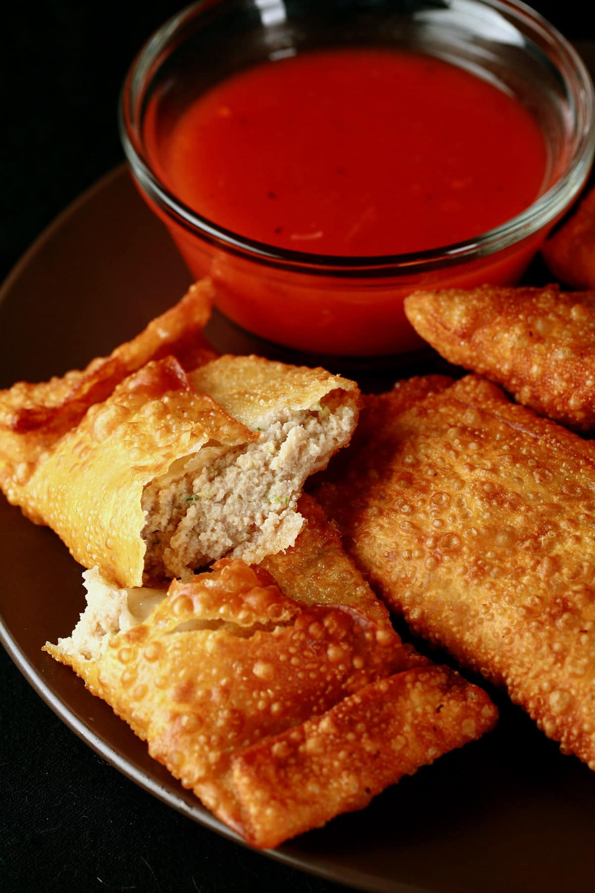 A small round plate holds several Halifax style egg rolls, next to a small bowl of deep orange plum sauce.