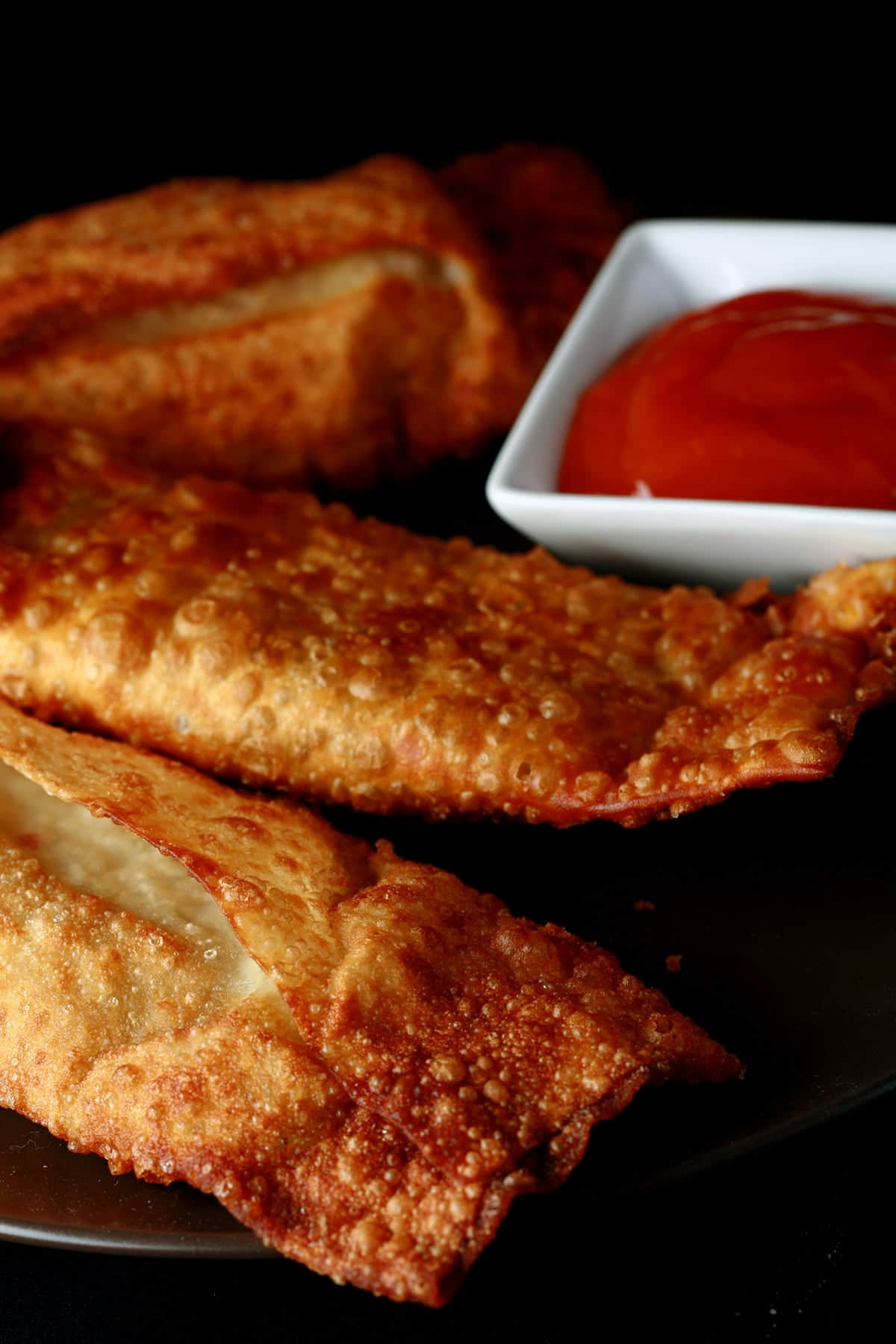 A small round plate holds several halifax styleegg rolls, next to a small bowl of deep orange plum sauce.