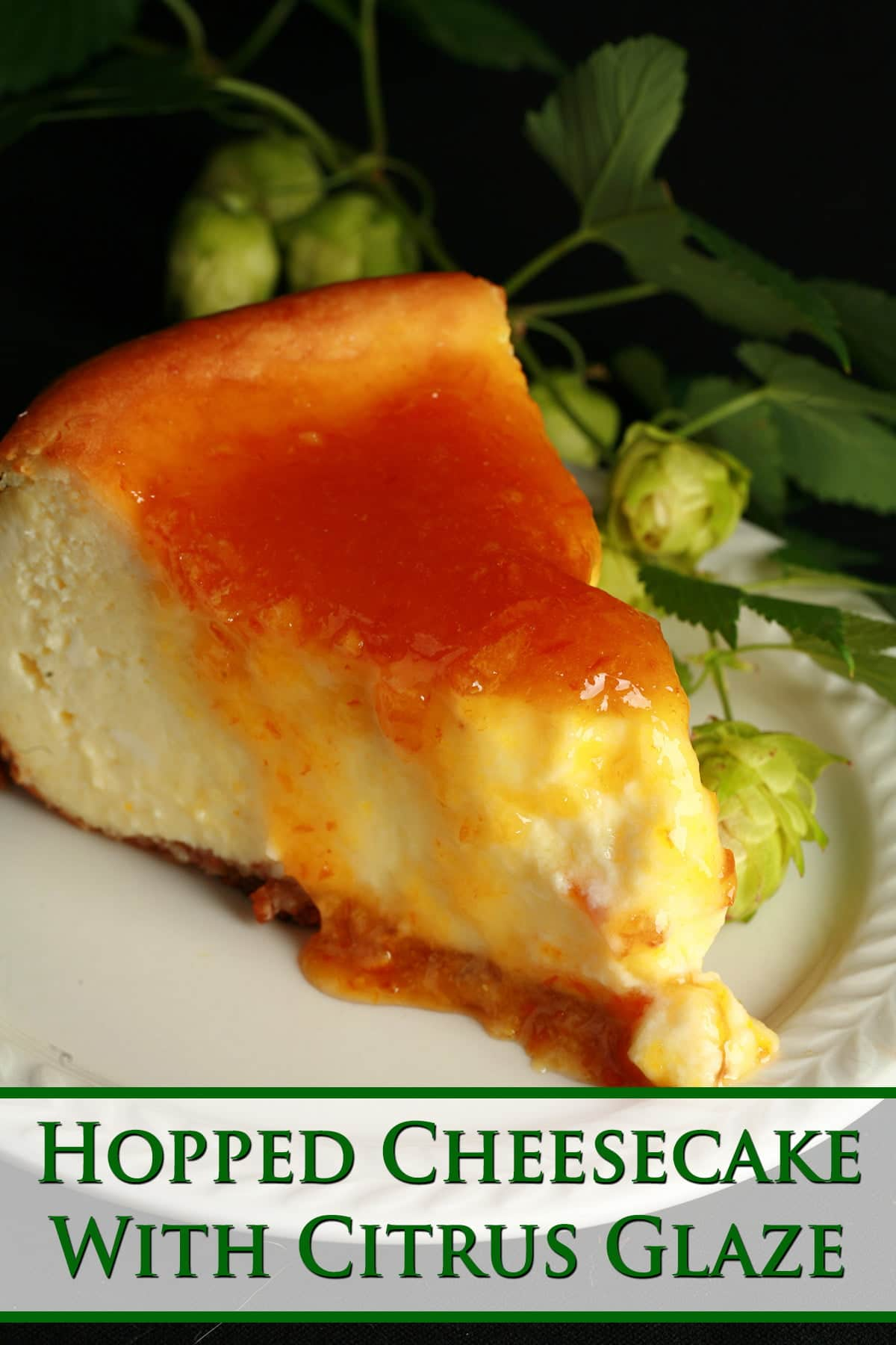 A slice of hop cheesecake with citrus glaze. The cheesecake is very pale yellow, topped with a bright orange glaze. It sits on a white plate, with a piece of fresh hop bine next to it.
