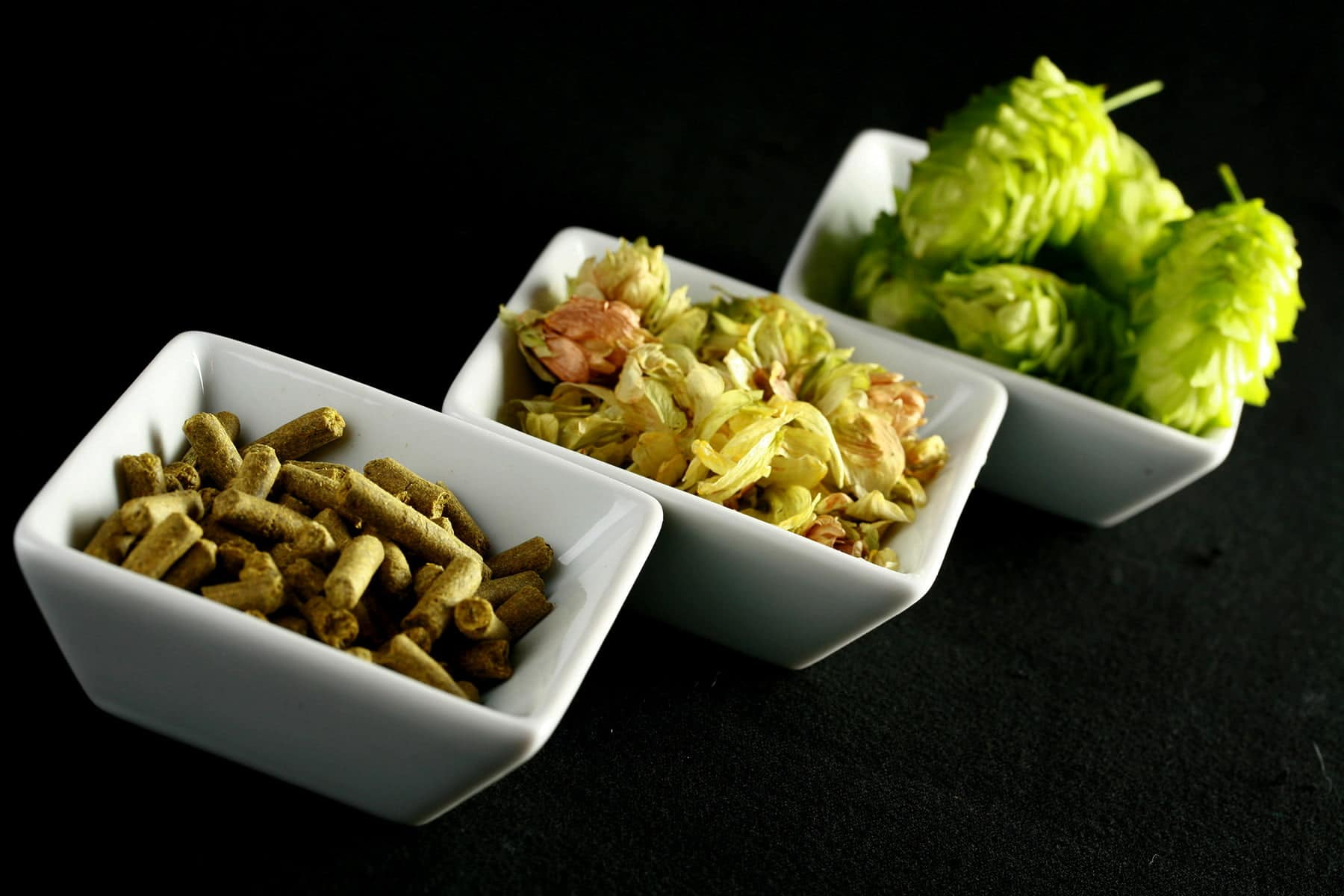 3 small white bowls hold hops in the 3 forms: Pellets, leaves, and fresh.