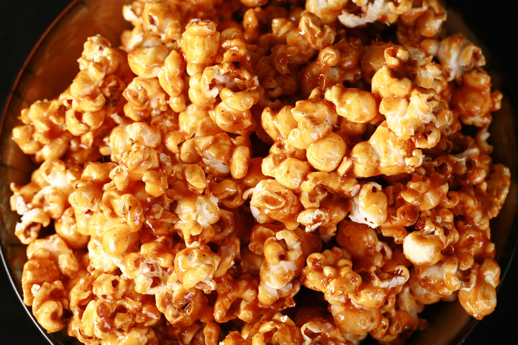 Close up photo of a bowl of caramel popcorn. Spices are visible throughout the caramel.
