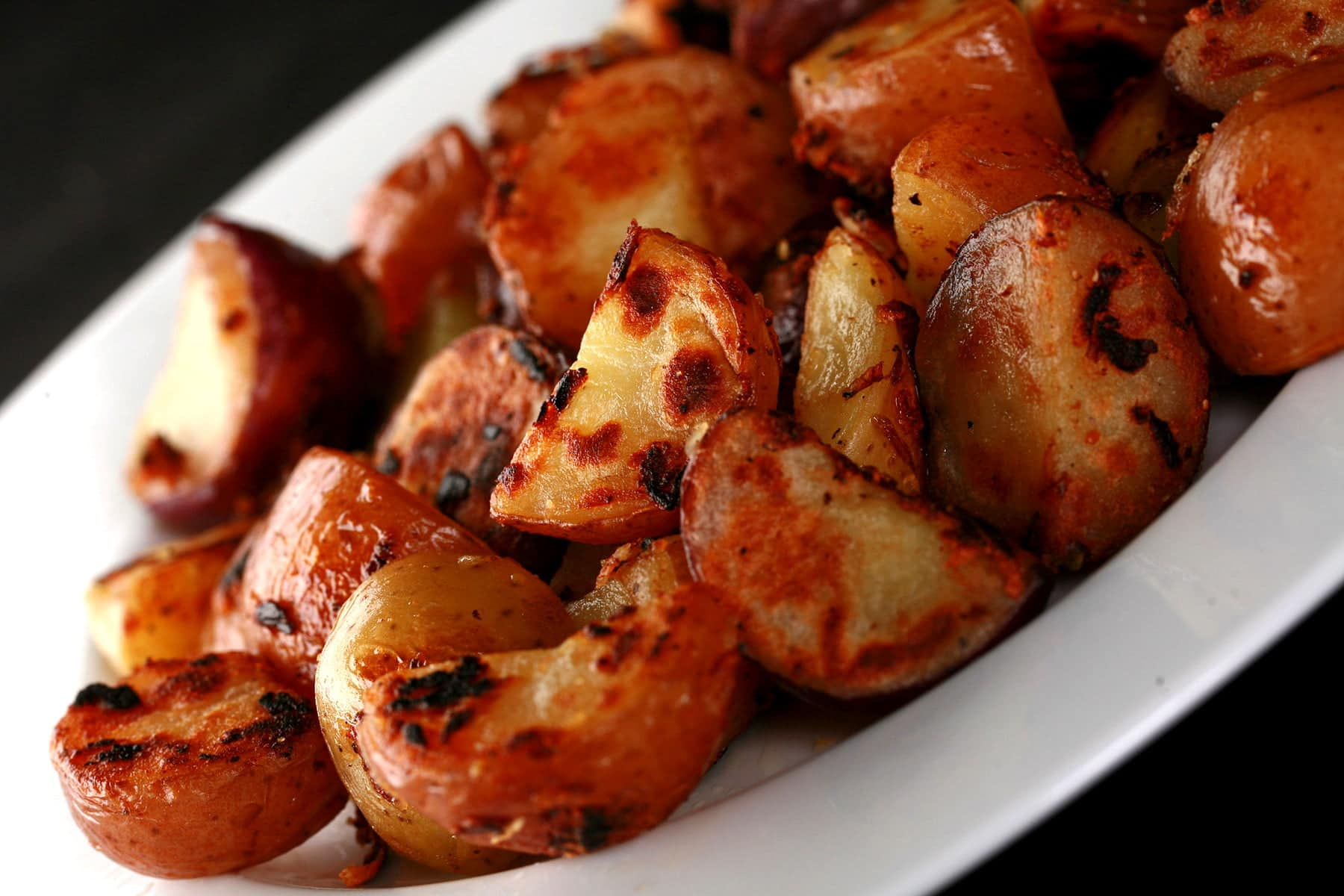 A white plate with a large helping of the BEST hash browns ever - chunks of red potatoes with charring and blistering on the surfaces.