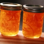 A row of small jars of clementine marmalade.