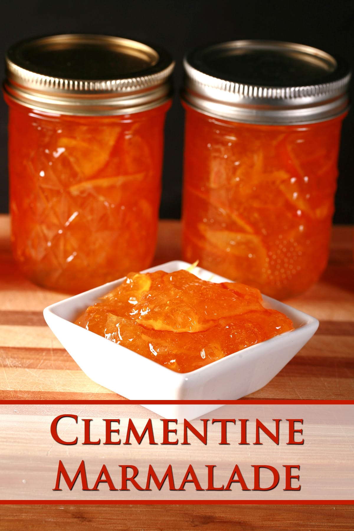 A row of small jars of clementine marmalade, with a small dish of marmalade in front.