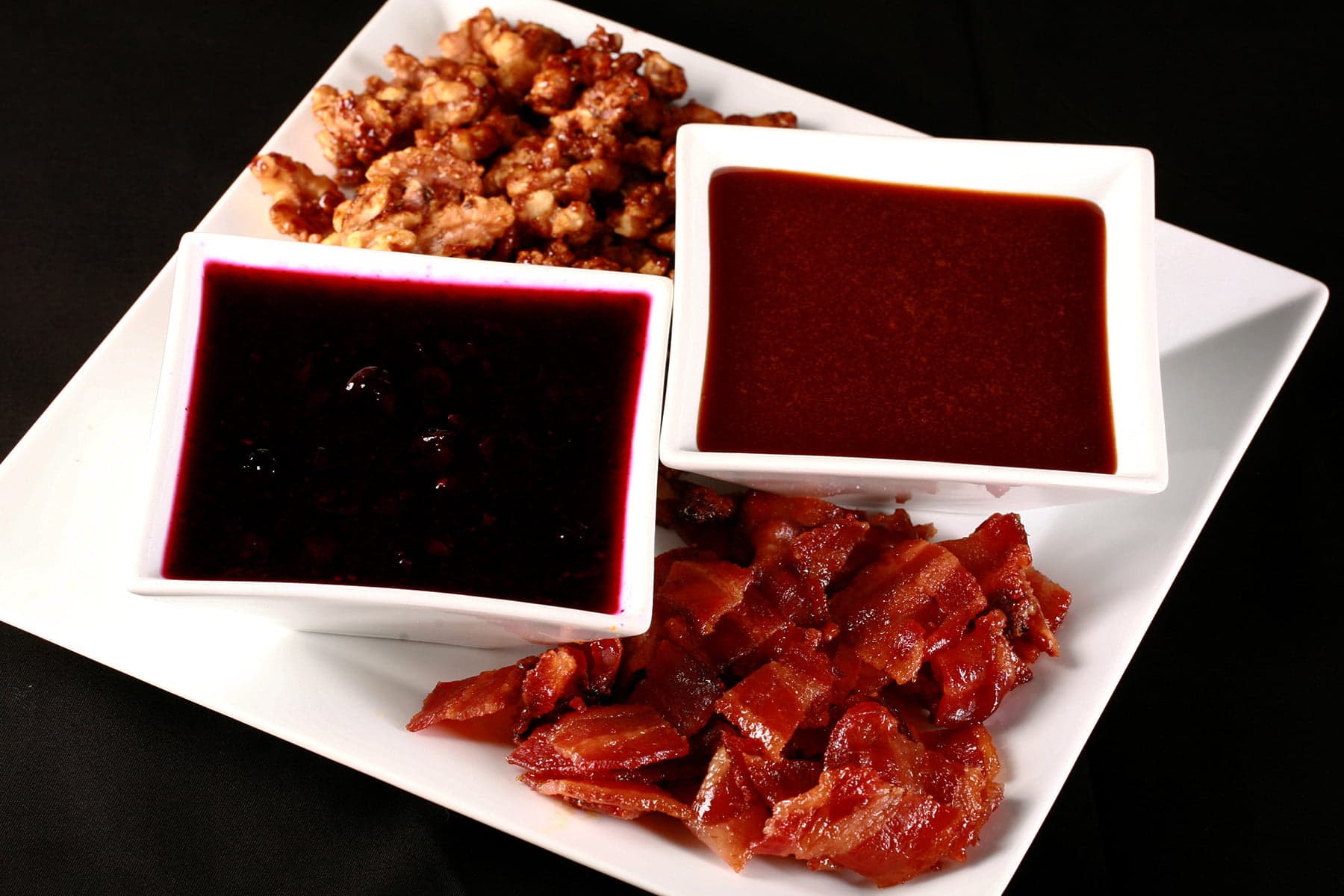 A large square white plate with ice cream toppings arranged on it.  Two square bowls hold sauces - blueberry and salted caramel - while candied bacon is in one corner, and candied nuts are piled in another corner.