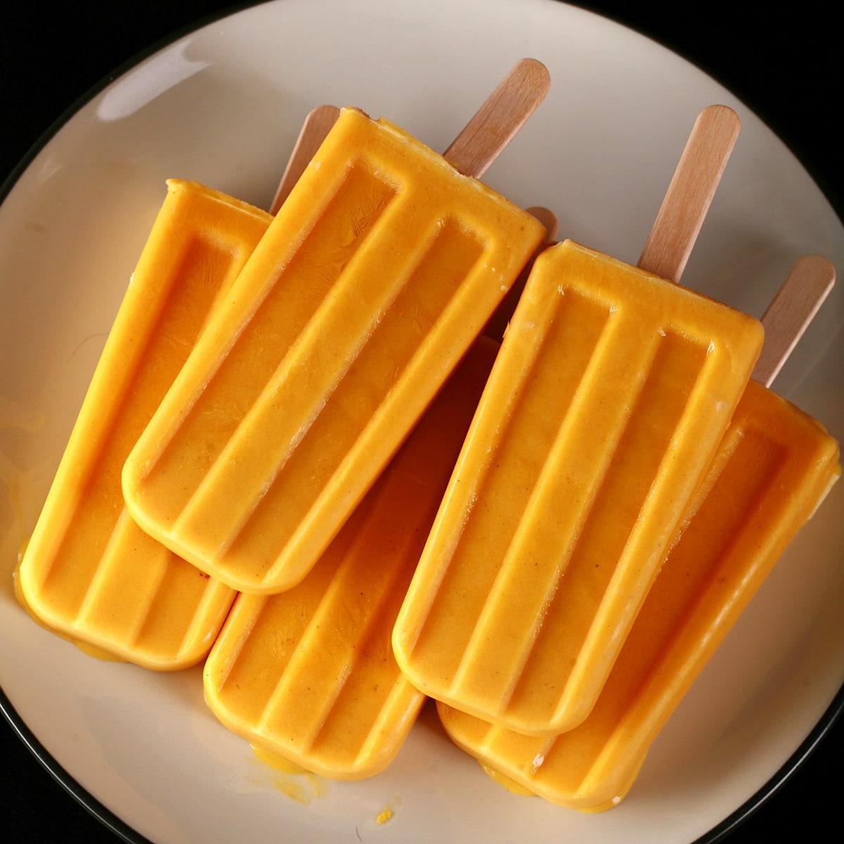 Several deep orange-yellow Mango Lassi Popsicles on a white plate.