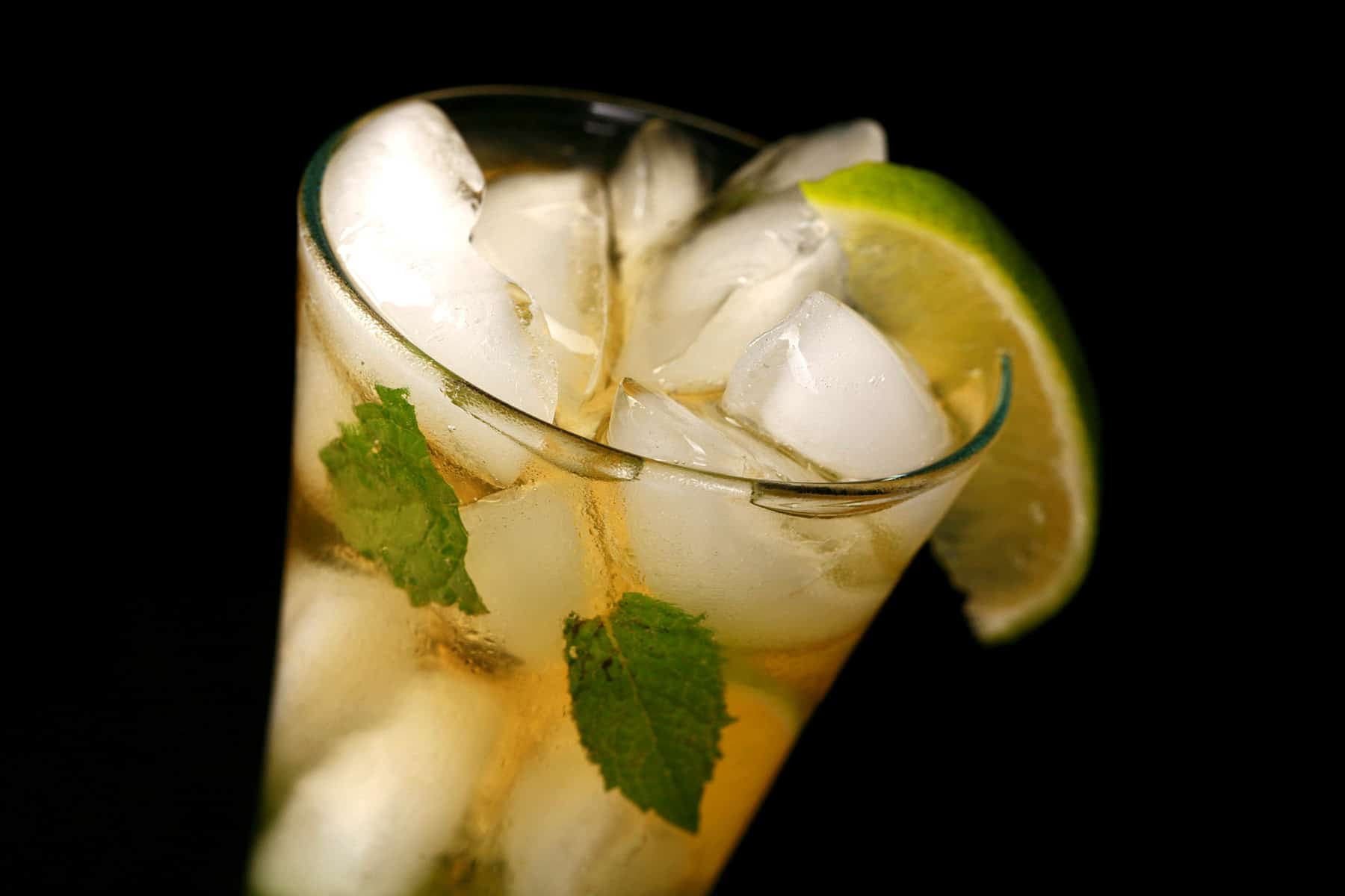 A close up view of Marie's Mojito Recipe - A tall glass with ice, limes, and mint in it, along with a pale amber liquid. It is garnished with a slice of lime.