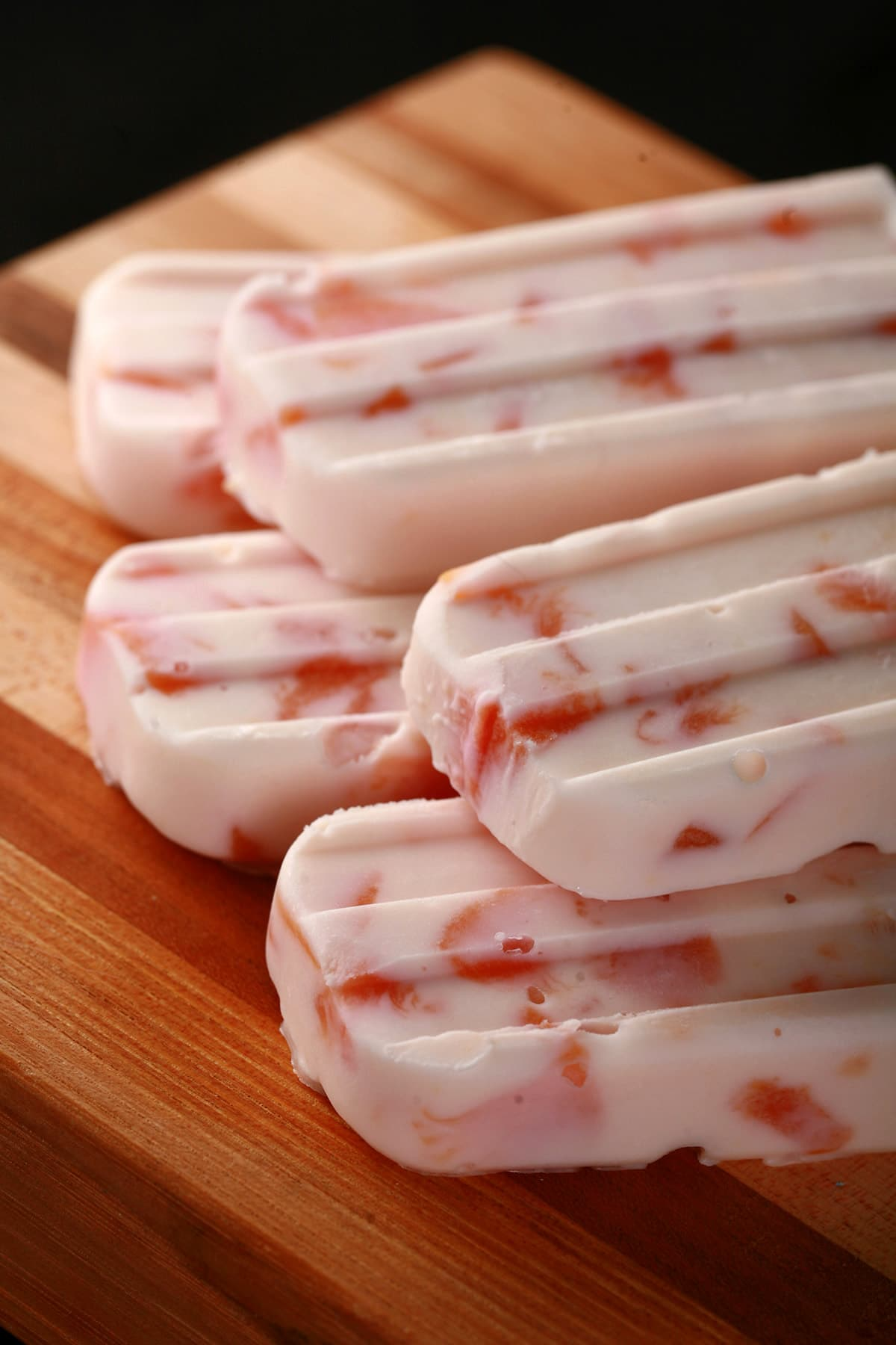 Southern Comfort Peaches N Cream Popsicles, laid out on a striped wooden cutting board.