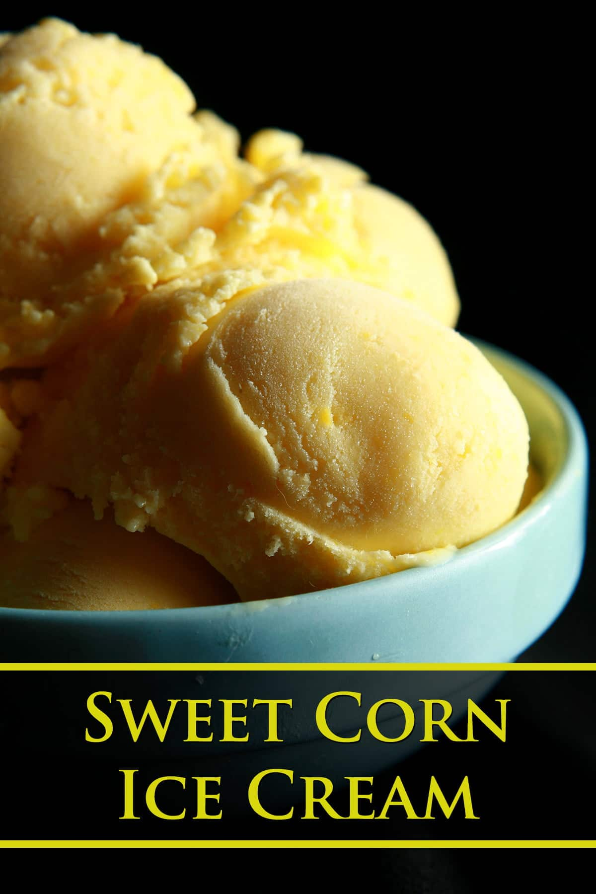 A small blue bowl, piled high with scoops of a yellow coloured sweet corn ice cream.