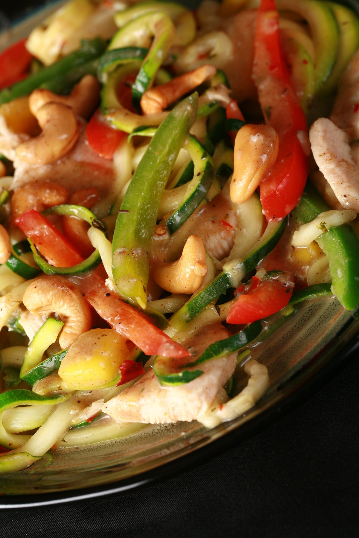 A plate of tropical chicken zoodles. Spiralized zucchini, pineapples, red pepper, cashews, and more.