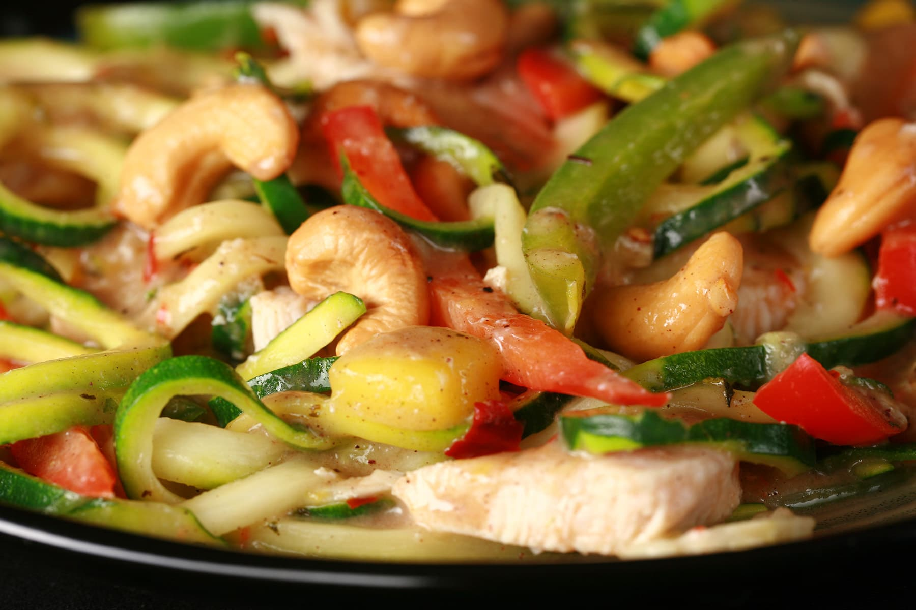 A plate of tropical chicken zoodle stir fry. Spiralized zucchini, pineapples, red pepper, cashews, and more.