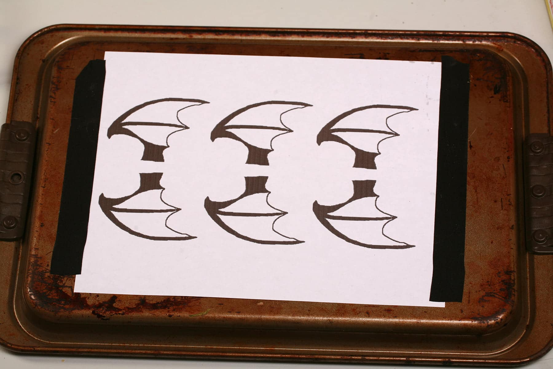 A printout of 3 pairs of bat wings are taped onto the back of a baking sheet.