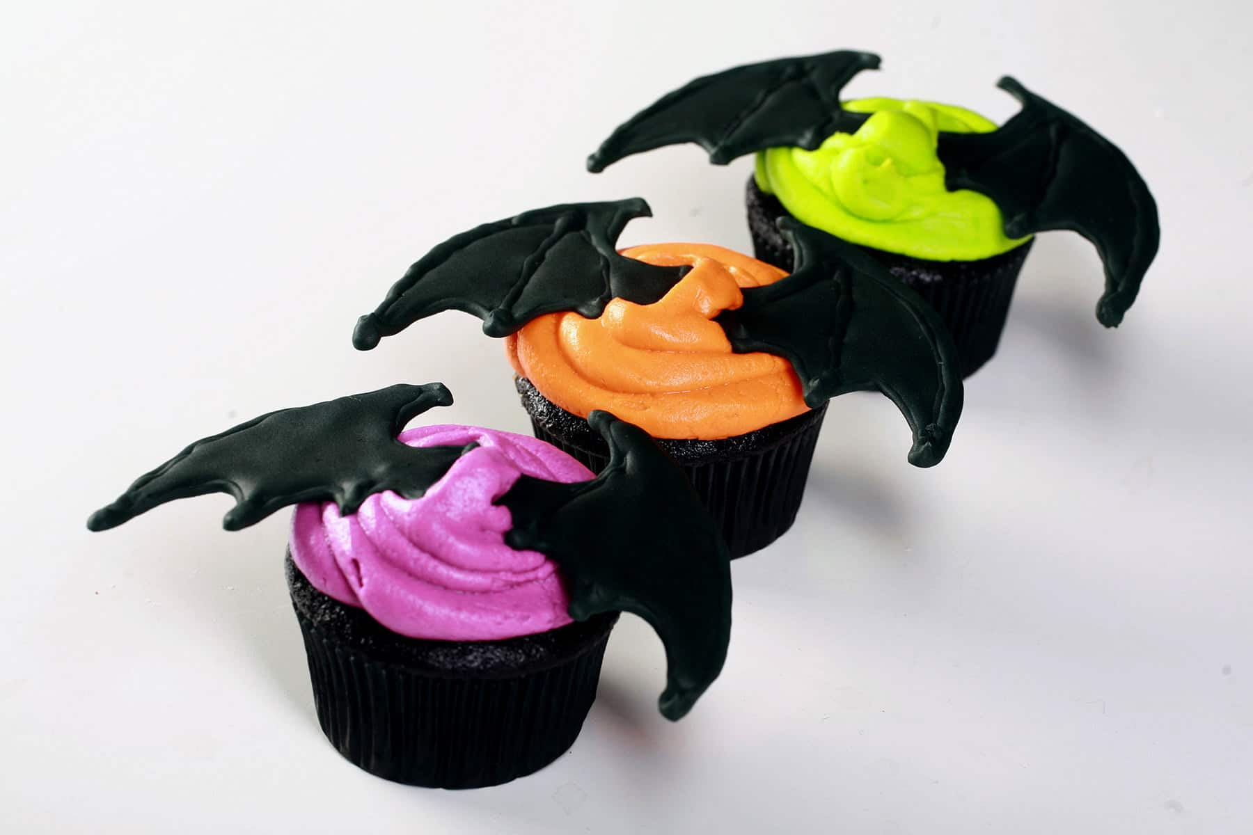 2 Black velvet cupcakes, frosted with bright icing - electric purple, lime green, and orange - and topped with a 3D pair of royal icing bat wings.