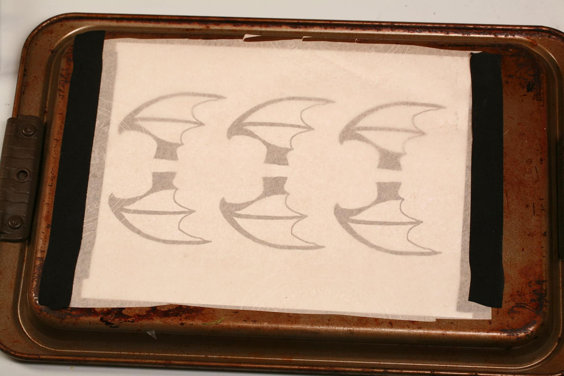 A printout of 3 pairs of bat wings are taped onto the back of a baking sheet, then covered with a sheet of parchment paper.