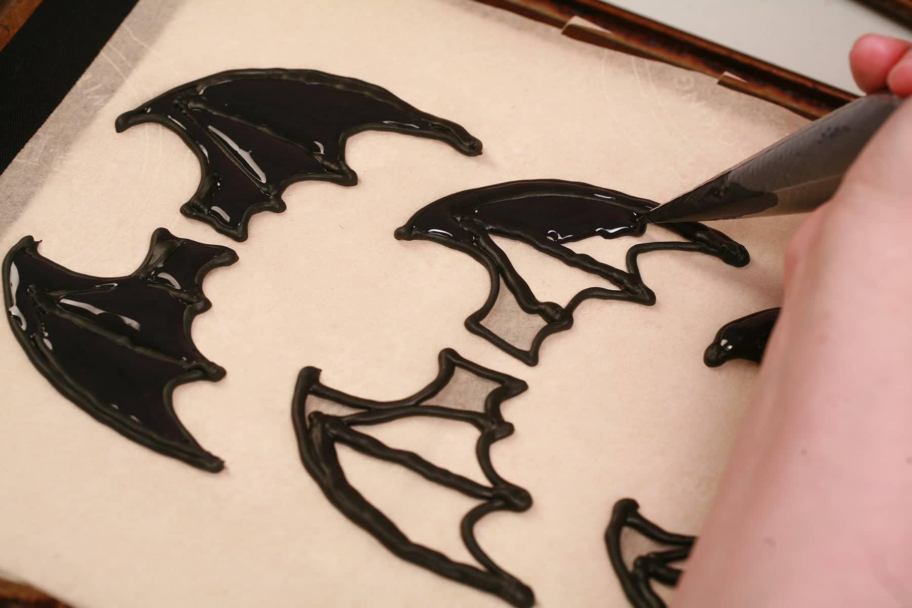 A hand uses a pastry bag of black royal icing to pipe bat wings on a parchment lined baking sheet.