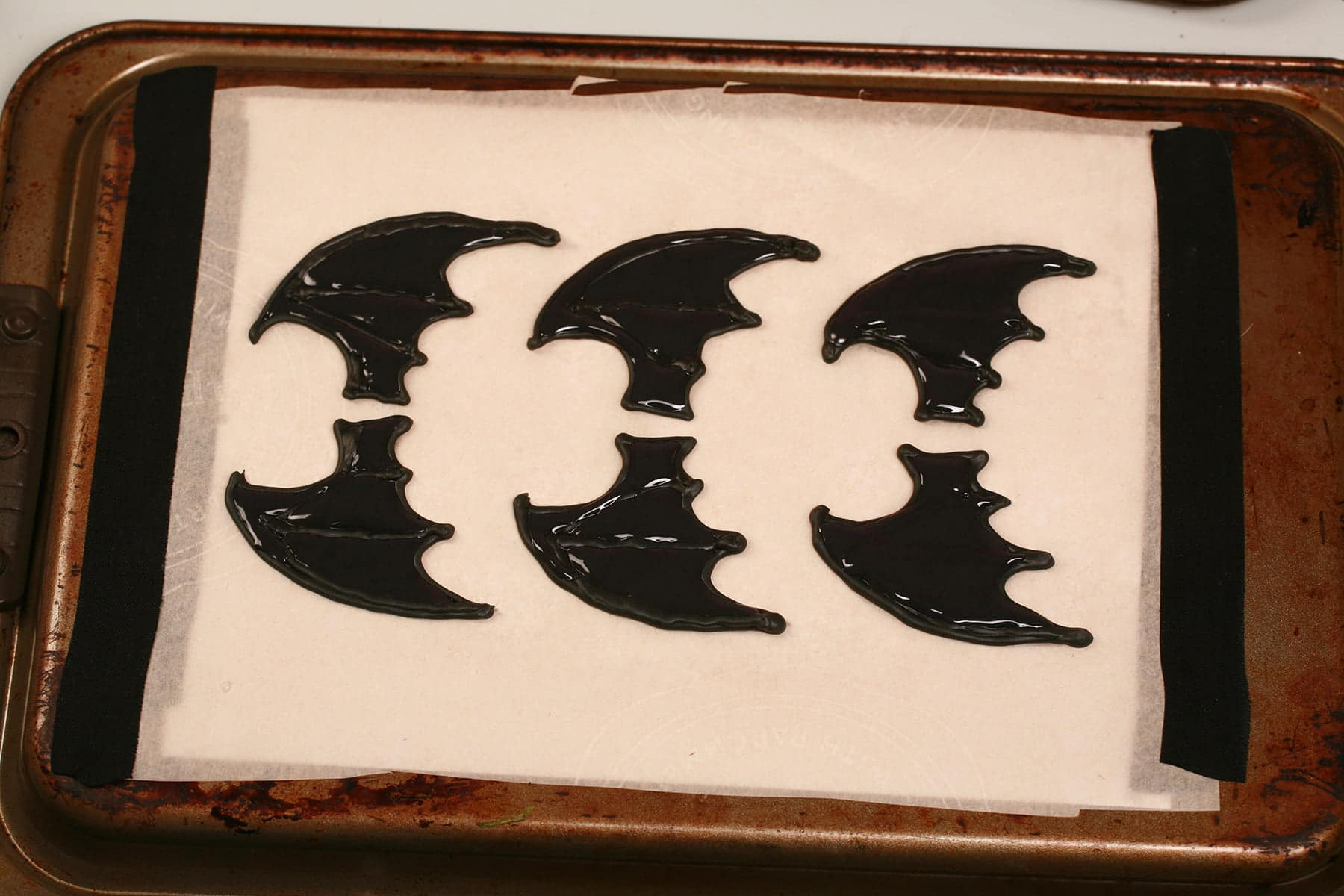3 sets of black frosting bat wings, piped on a parchment lined baking sheet.