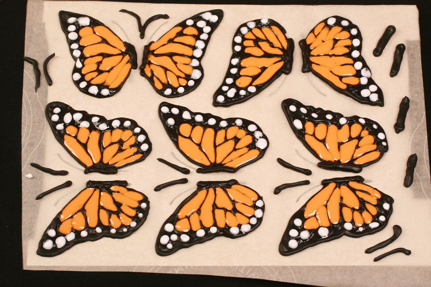 A tray of frosting piped monarch butterfly wings.