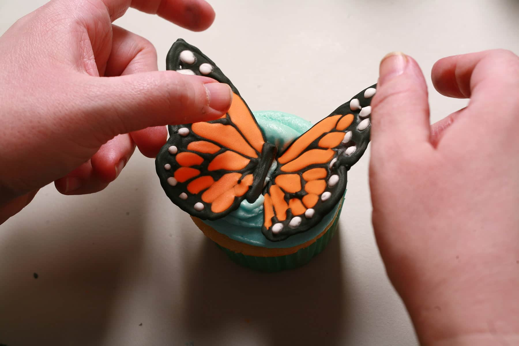 Two hands place a set of monarch butterfly wings on a cupcake iced with blue frosting.