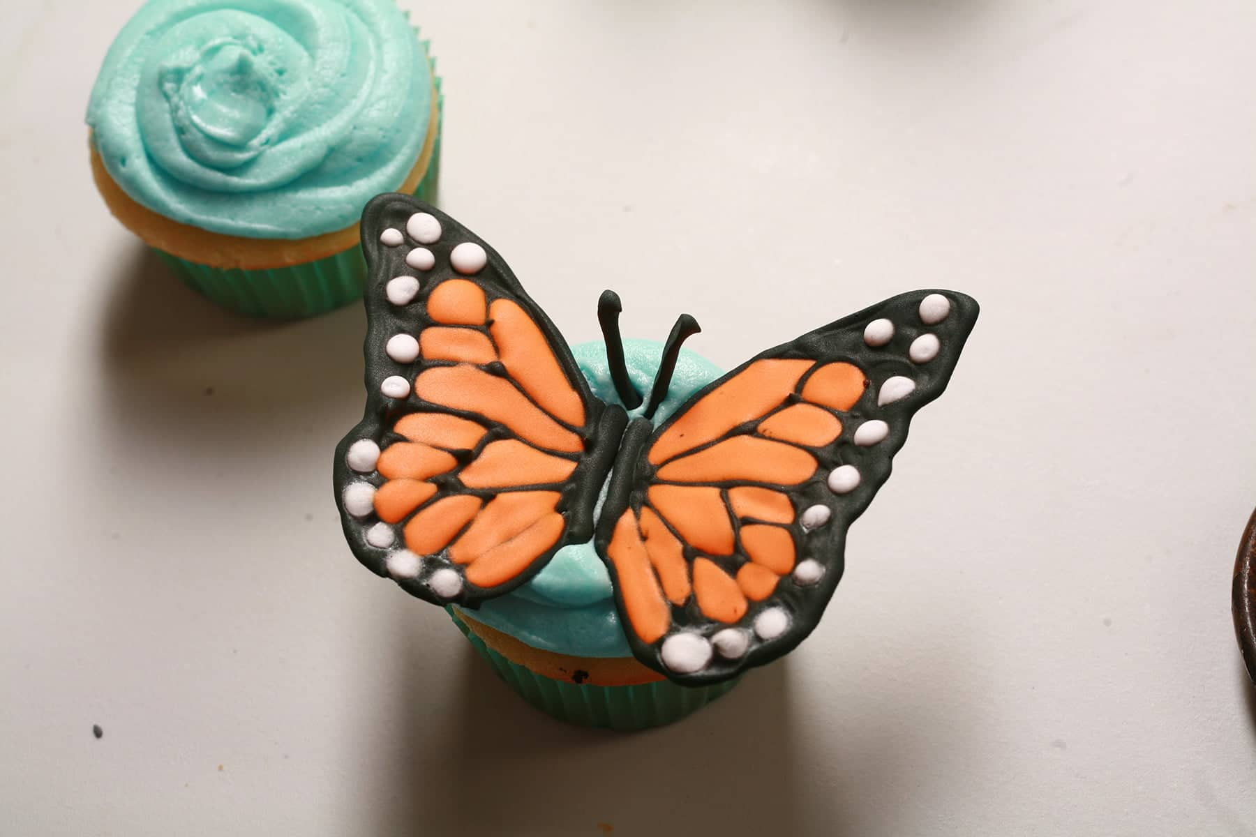 Two cupcakes frosted with sky blue icing. One has a set of frosting monarch butterfly wings on top of it.