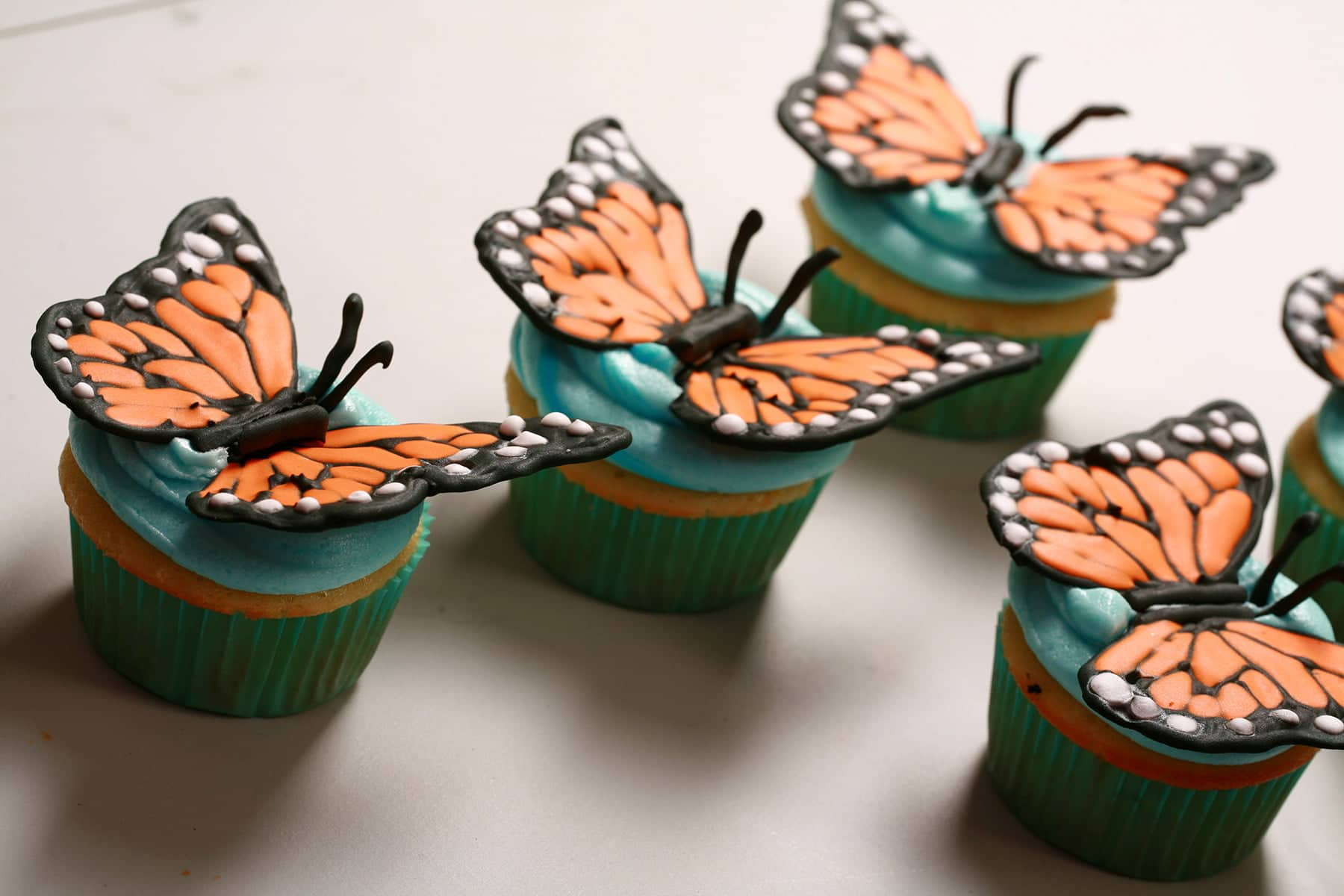 A set of 4 vanilla cupcakes with royal icing monarch butterfly wings on top of each.  They are position to look like they are flying away from the camera.