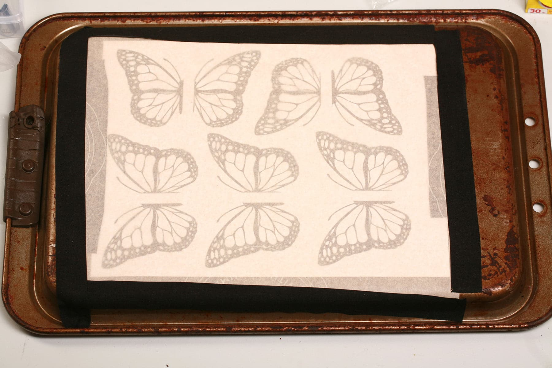 A page of butterfly wing designs is taped to the back of a baking sheet, and covered with parchment paper.