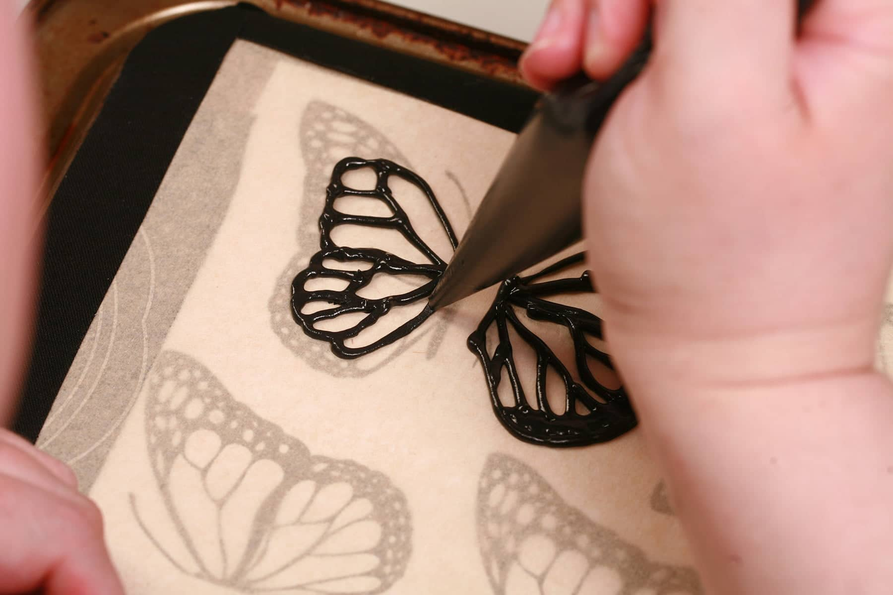 A hand uses a pastry bag full of black royal icing to pipe the outlines of butterfly wings on the back of a baking sheet.