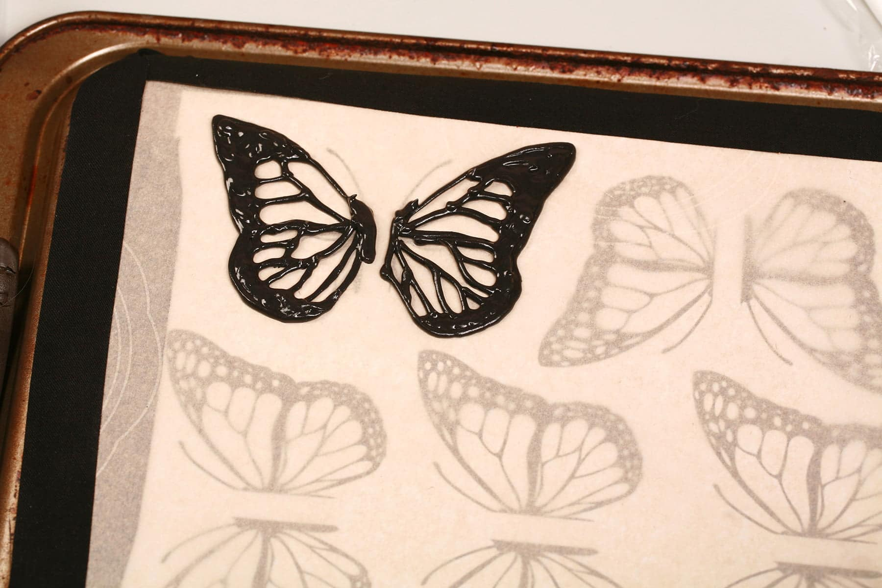 A set of butterfly wing outlines, piped on a parchment lined baking sheet.