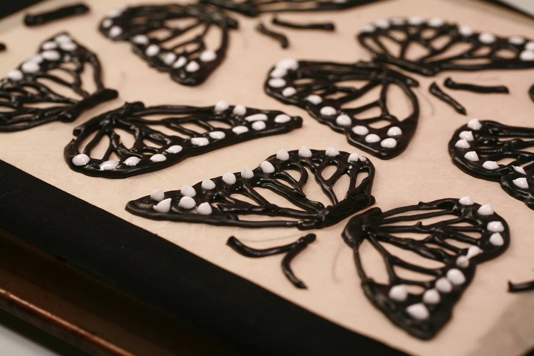 A close up view of black and white frosting outlines of monarch butterfly wings, piped on the back of a baking sheet.