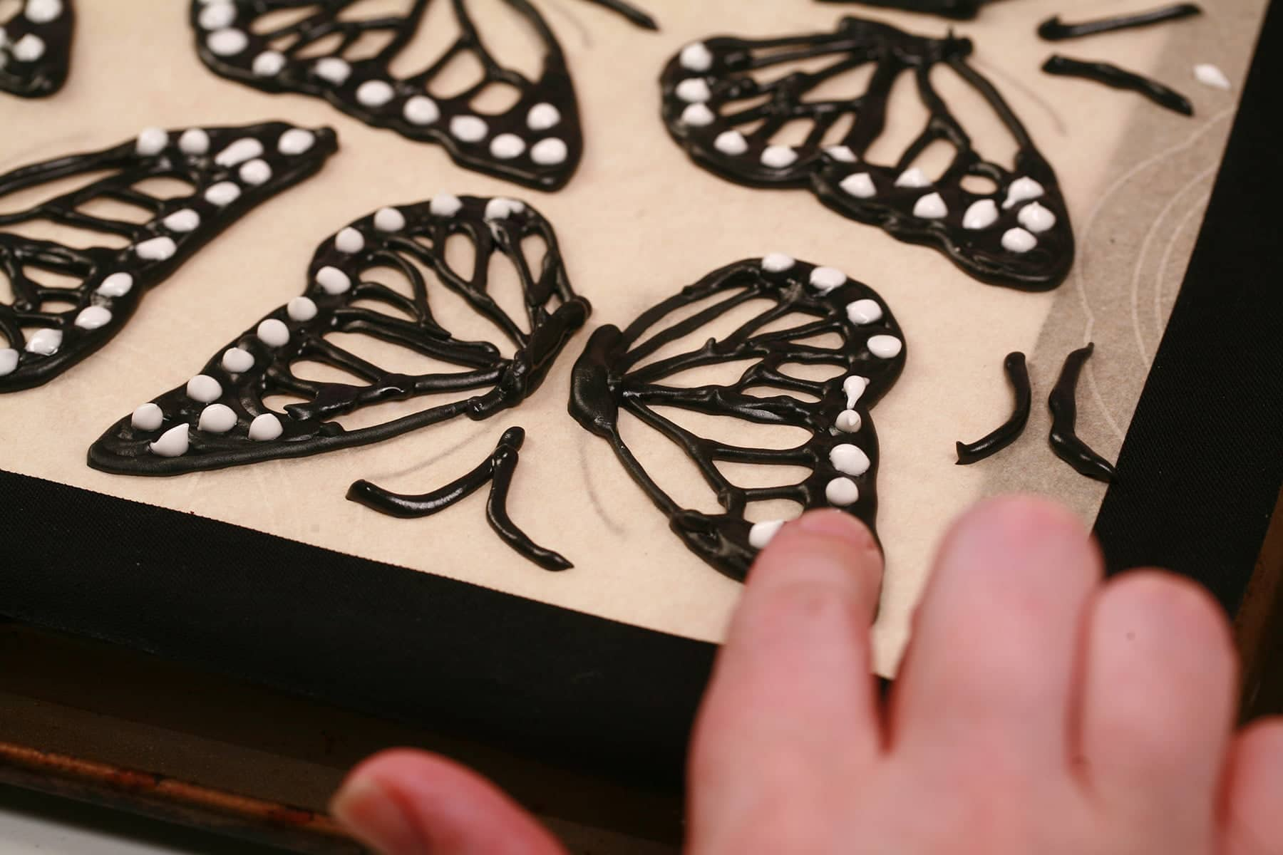 A finger is shown gently tapping down the peaks of white royal icing on a butterfly wing.