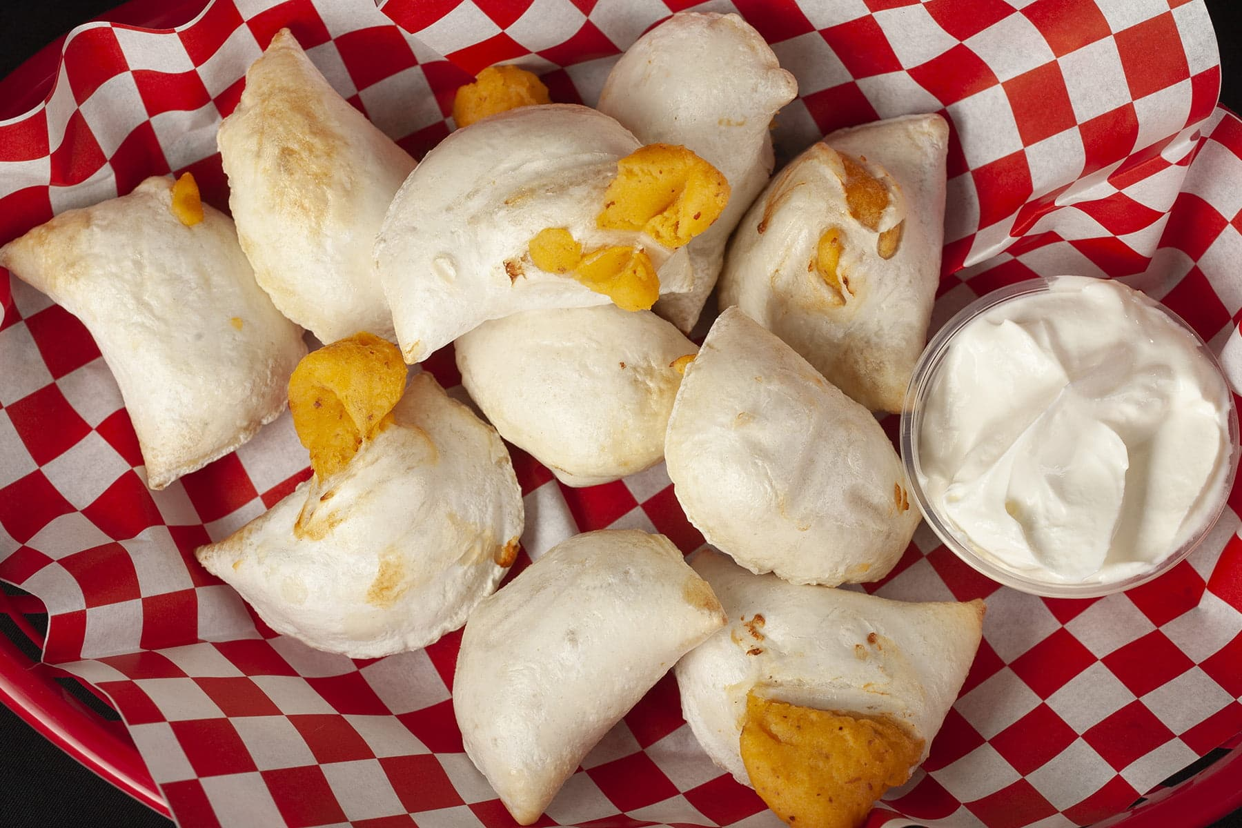 A basket of perogies. Most are split open, with cheese filling oozing out.